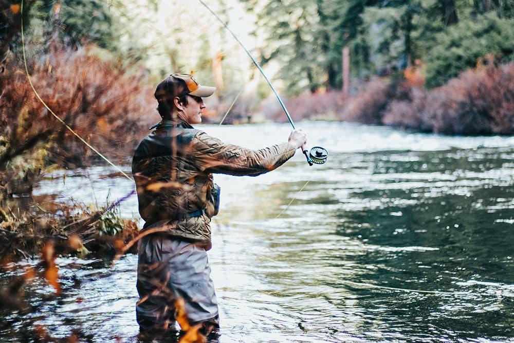 Чоловік ловить рибу в ріці