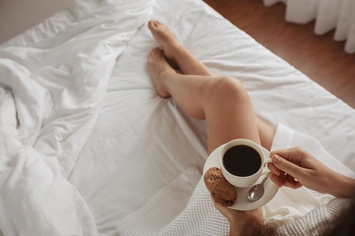 Фото з чашкою кави на ліжку